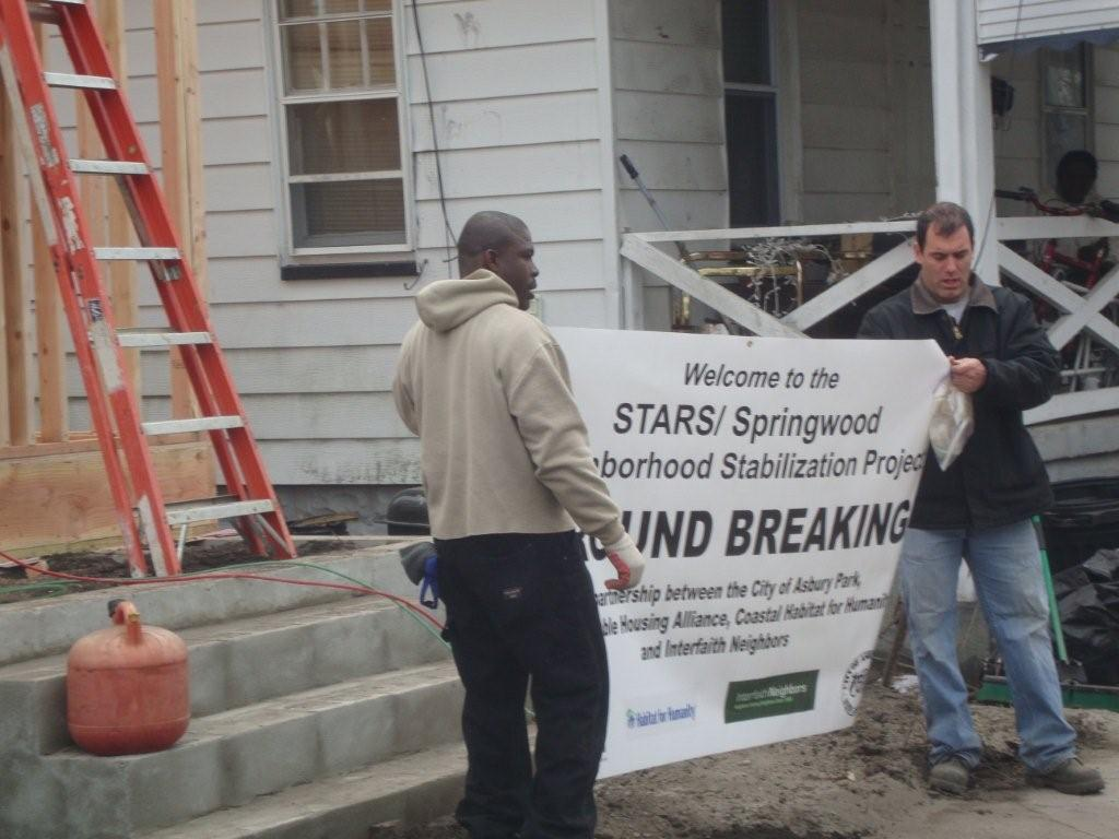 Two Men Carrying a Ground Breaking Sign